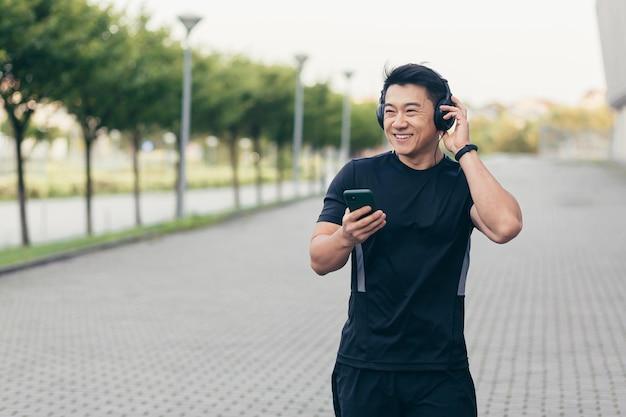 Un athlète asiatique masculin lors d'une course matinale dans le parc près du stade écoute de la musique et des podcasts dans de gros écouteurs utilise le téléphone