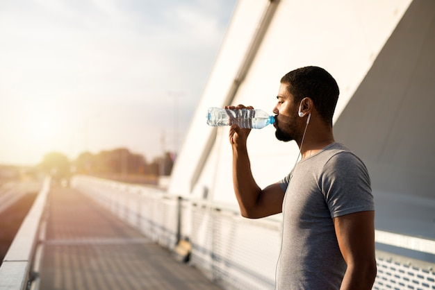 Athlète attrayant tenant une bouteille d'eau et buvant avant l'entraînement