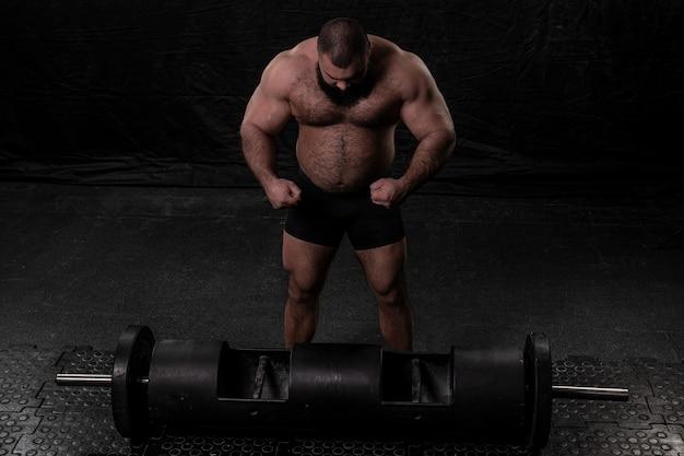 Un athlète aux muscles volumineux se tient à côté d'un appareil de puissance extrême