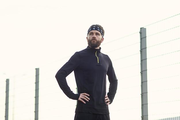 Athlète barbu masculin en uniforme de sport et bandana après un entraînement intensif sur le terrain de jeu
