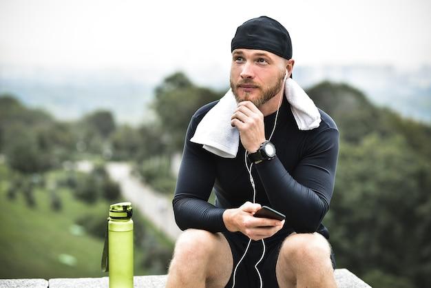 Athlète barbu musclé avec une serviette vérifiant les calories brûlées sur son smartphone après une bonne séance d'entraînement dans le parc de la ville.