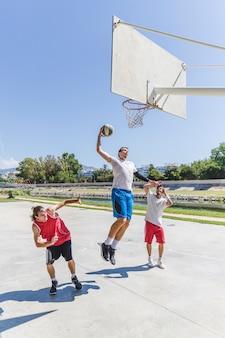 Athlète de basket-ball de rue effectuant énorme slam dunk sur le terrain