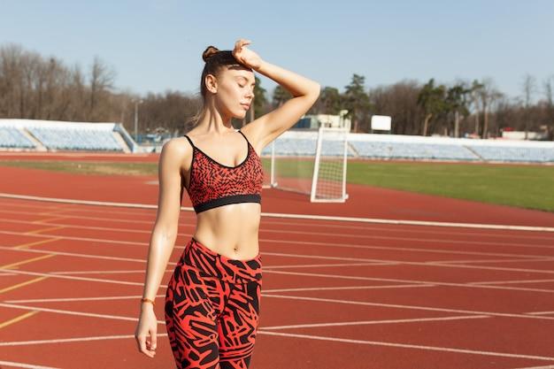 Athlète belle fille caucasien au repos après avoir fait du jogging sur une piste de course.