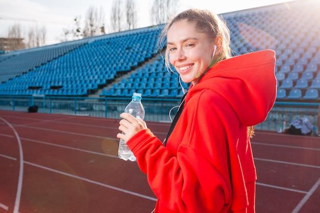 Athlète belle fille tient dans ses mains une eau dans une bouteille en plastique