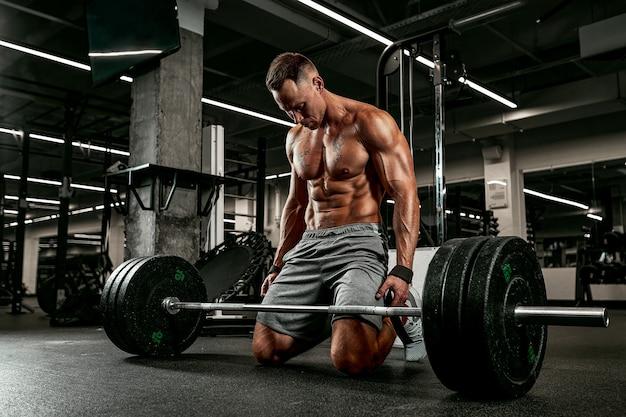Athlète blessé avec une barre se préparant à une séance d'entraînement dans la salle de sport pour le sport, le fitness, l'haltérophilie, les blessures sportives et les personnes.