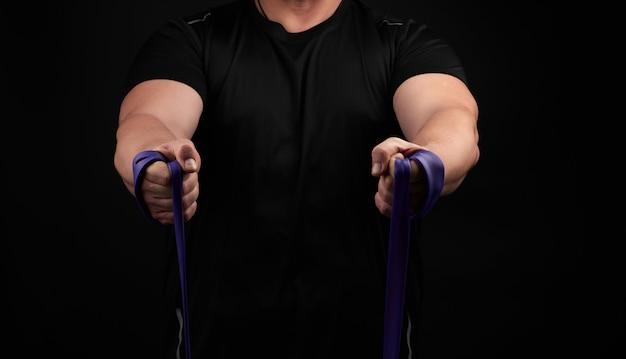 Athlète avec un corps musclé dans des vêtements noirs fait des exercices physiques avec du caoutchouc violet