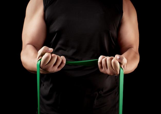 Athlète avec un corps musclé en vêtements noirs faisant des exercices physiques avec du caoutchouc vert