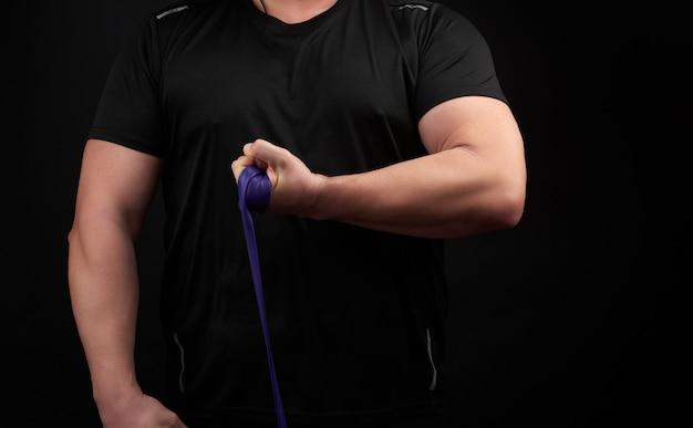 Athlète avec un corps musclé en vêtements noirs fait des exercices physiques