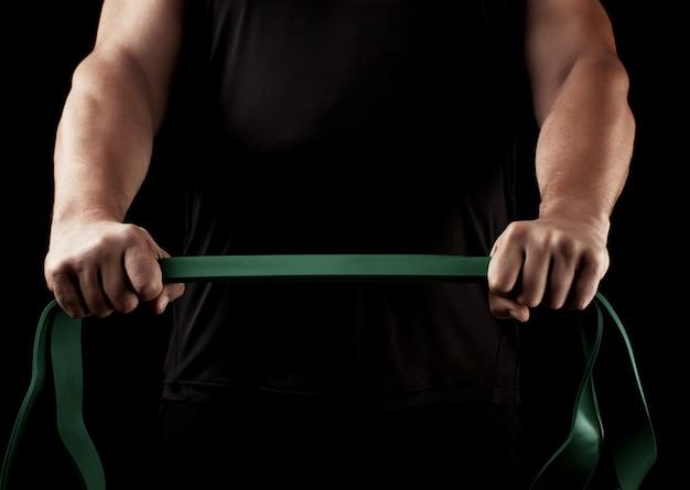 Athlète avec un corps musclé vêtu de noir fait des exercices physiques avec du caoutchouc vert