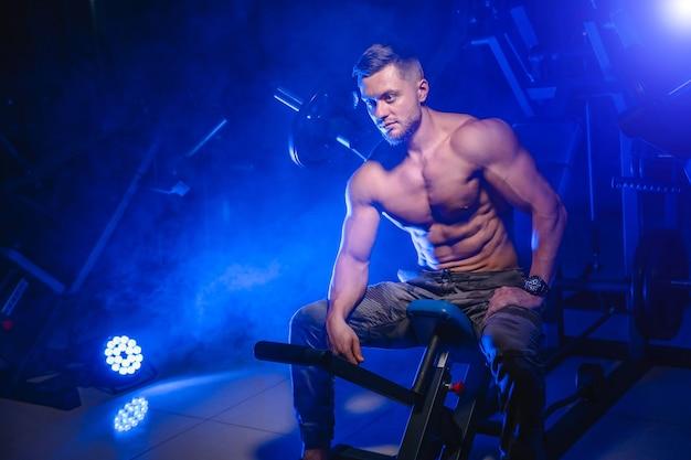 Athlète avec un corps solide au repos après un entraînement dans une salle de sport