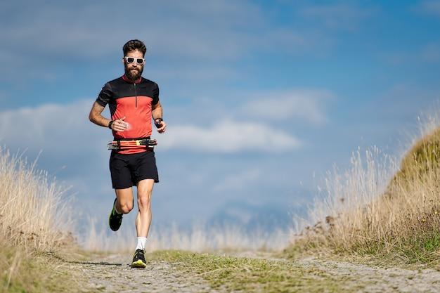Un athlète coureur avec une barbe s'entraîne sur une route de montagne