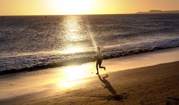 Athlète de coureur courant au bord de la mer. femme fitness silhouette lever du soleil jogging entraînement concept de bien-être