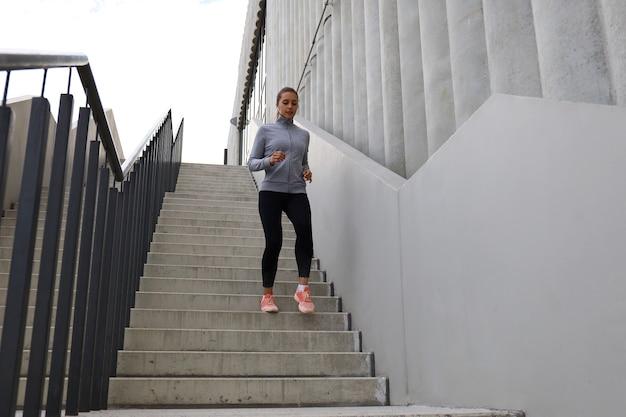 Athlète de coureur courant dans les escaliers. la forme physique de la femme fait du jogging à l'extérieur.