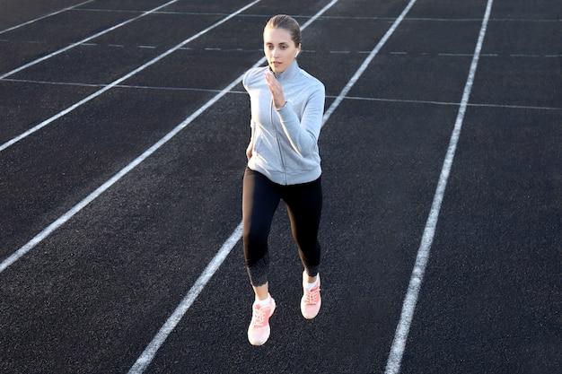 Athlète coureur courant sur piste d'athlétisme entraînant son cardio dans le stade. jogging à rythme rapide pour la compétition.