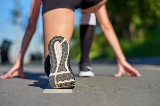 Athlète coureur pieds courir sur tapis roulant gros plan sur la chaussure
