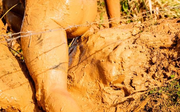 Athlète de course à pied traversant la flaque sale dans un coureur de boue.