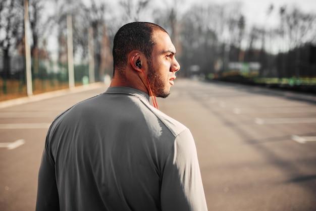 Athlète dans les écouteurs avant de faire du jogging dans le parc