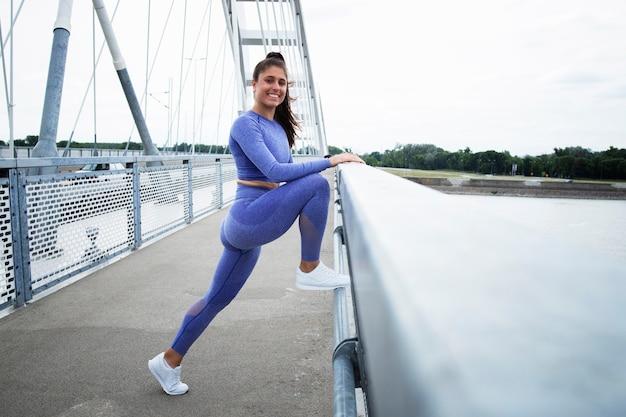 Un athlète étire les jambes et s'échauffe avant de courir.
