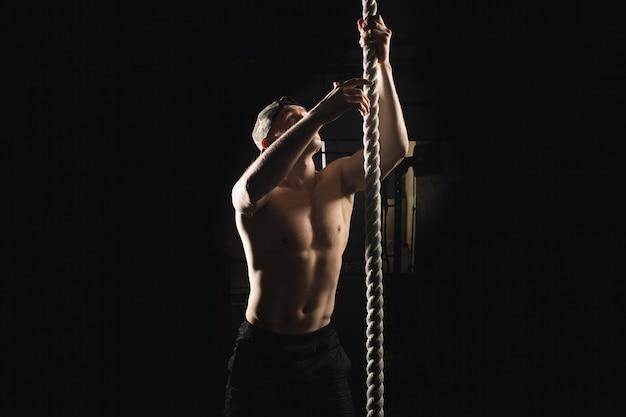 Athlète faisant de l'exercice de montée de corde de remise en forme dans la salle de gym