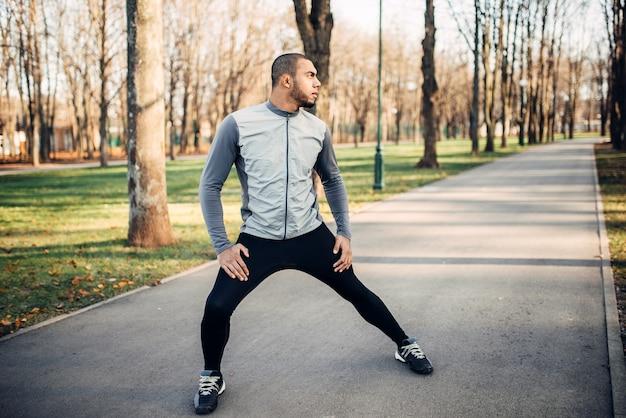 Athlète faisant des exercices d'étirement avant de courir