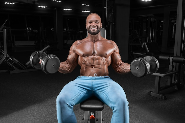 L'athlète fait l'exercice dans le gymnase. soulever des haltères assis sur un banc