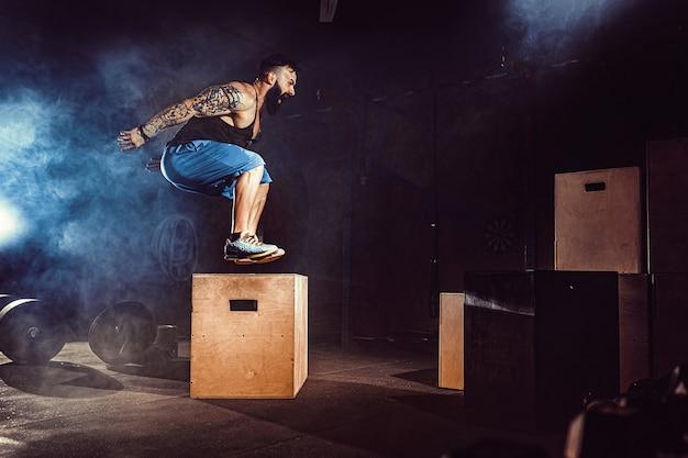 L'athlète a fait de l'exercice. sauter sur la boîte. phase de touché. coups de gym dans le ton sombre. fumée.