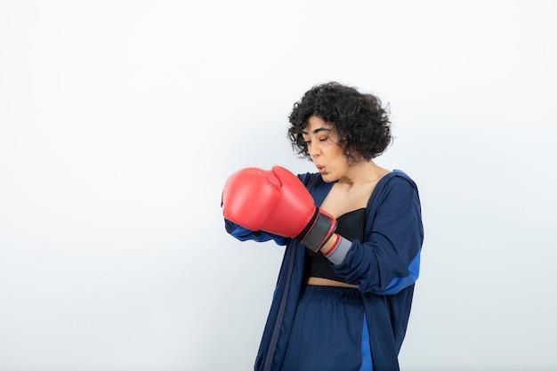 Athlète féminine aux cheveux bouclés décoller les gants rouges.