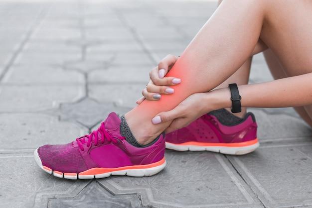 Athlète féminine ayant une blessure à la cheville assis sur le trottoir