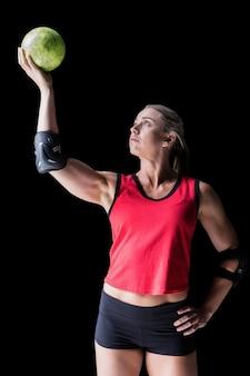 Athlète féminine avec coudière tenant le handball sur fond noir