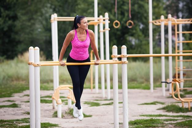Athlète féminine engagée sur la barre horizontale dans la rue