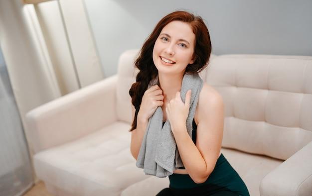 Une athlète féminine est assise sur le canapé et se repose après un entraînement intense avec une serviette de sweatconce...