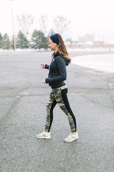 Athlète féminine exerçant dans la rue en hiver