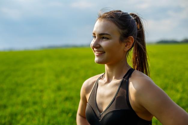 Une athlète féminine fait de l'échauffement à l'extérieur, des exercices pour les muscles. une jeune femme fait du sport, un mode de vie sain, un corps athlétique. elle est en tenue de sport, haut noir et short. notion de sport.