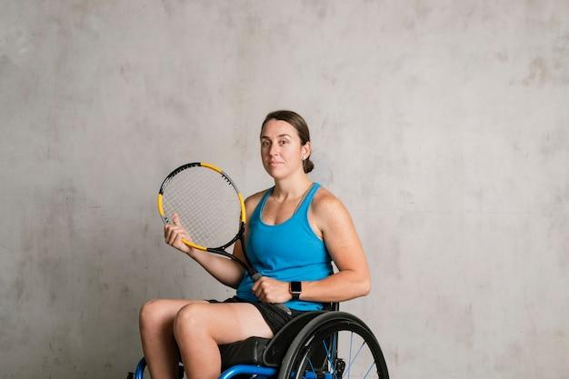 Athlète féminine en fauteuil roulant tenant une raquette de tennis