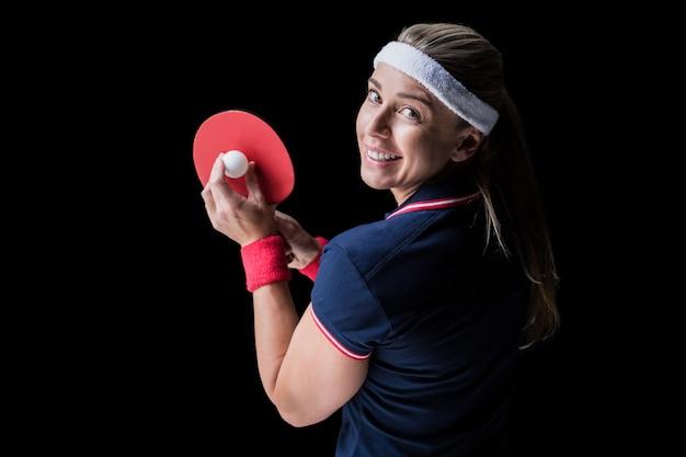 Athlète féminine jouant au ping-pong sur fond noir