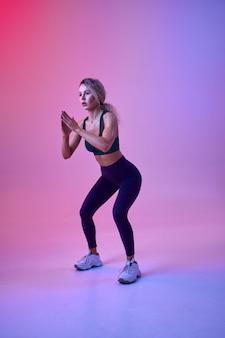 Athlète féminine mince faisant de l'exercice en studio, fond néon. sportive de remise en forme à la séance photo, concept sportif, motivation de style de vie actif