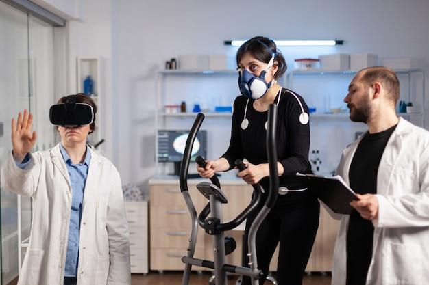 Athlète féminine de performance s'exécutant sur un entraînement croisé avec exercice de masque, électrodes attachées. docteur en sciences du sport portant des lunettes de réalité virtuelle testant la biomécanique corporelle en laboratoire.