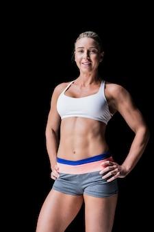 Athlète féminine posant les mains sur les hanches sur fond noir