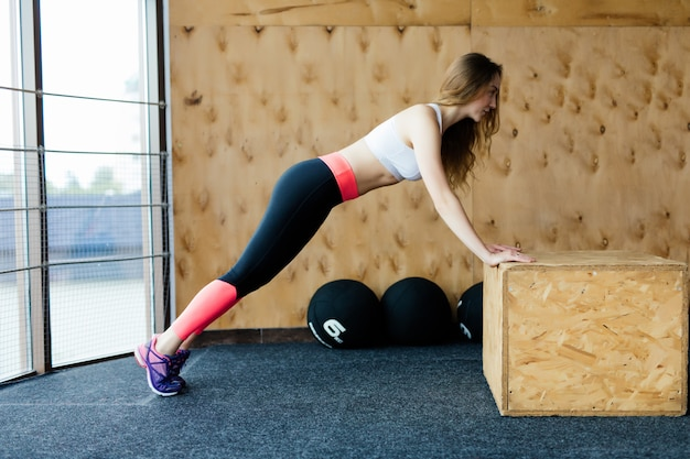 Athlète féminine pratiquant des pompes et des burpees dans une salle de sport