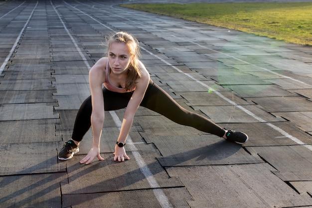 Athlète féminine prépare les jambes pour l'entraînement cardio. coureur de fitness faisant une routine d'échauffement. coureur de femme se réchauffer en plein air. athlète, étirage, échauffement, piste, courant, stade