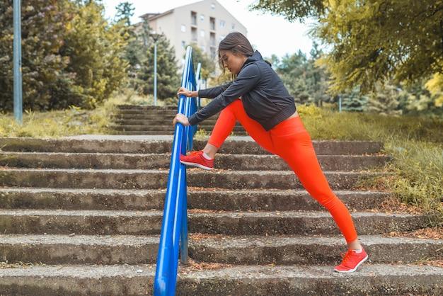 Athlète féminine qui s'étend dans le parc avant de courir.