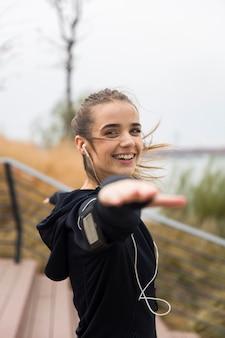 Athlète féminine qui s'étend ses bras tout en écoutant de la musique en plein air