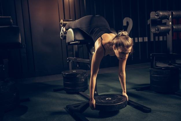 L'athlète féminine s'entraînant dur dans la salle de gym