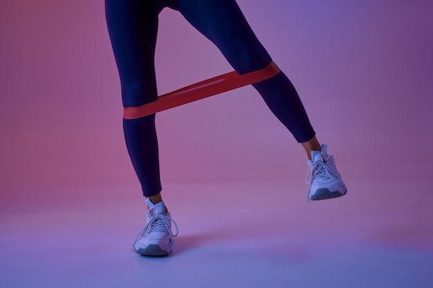 Athlète féminine sexy faisant de l'exercice avec du caoutchouc en studio, fond néon