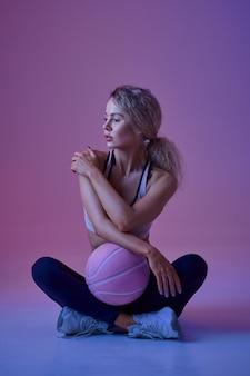Athlète féminine sexy pose avec ballon en studio, fond néon