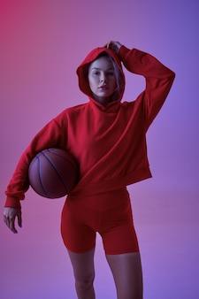 Athlète féminine sexy en sweat à capuche rouge pose avec ballon en studio, fond néon