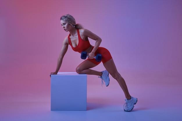 Athlète féminine sexy en tenue de sport rouge pose avec haltère au cube en studio, fond néon