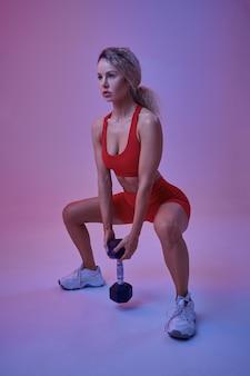 Athlète féminine sexy en tenue de sport rouge pose avec haltère en studio, fond néon