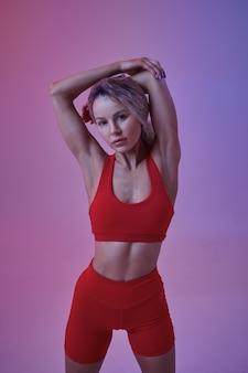 Athlète féminine sexy en tenue de sport rouge pose en studio, fond néon