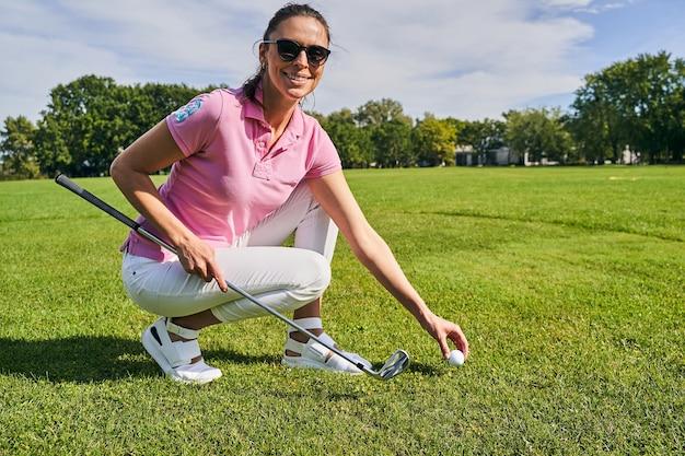 Athlète féminine souriante avec un club de golf dans la main gauche assise sur ses hanches